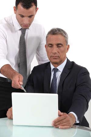 shirtsleeves: Executives looking computer project Stock Photo