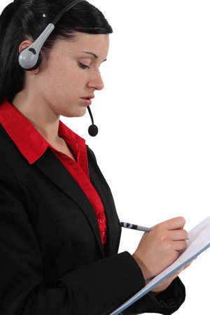 notecase: Woman with headset writing on notepad Stock Photo