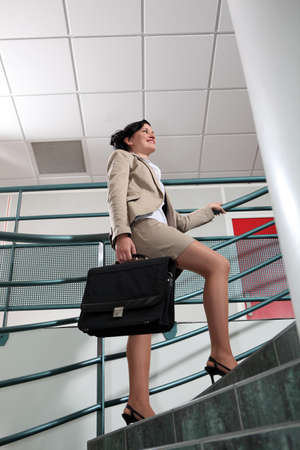 Businesswoman with briefcase climbing stairs photo