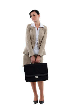 coy: Coy businesswoman stood with briefcase