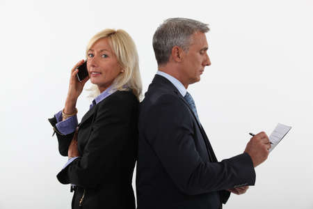 businesspartners: mature businessman and female partner standing back to back Stock Photo