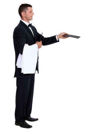Profile view of male waiter holding out menu photo