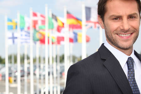 foreign trade: Executive in front of flags Stock Photo