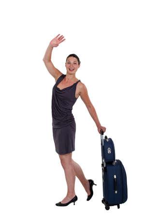 the farewell: mujer joven con equipaje agitando adiós Foto de archivo