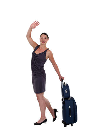 farewell: young woman with luggage waving goodbye Stock Photo