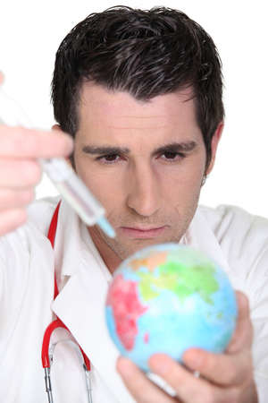 Doctor using syringe on a globe photo