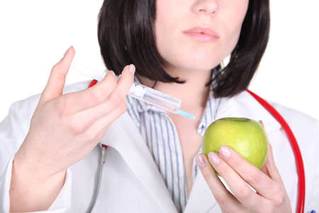 Doctor injecting hormone drugs into an apple Stock Photo - 18099812