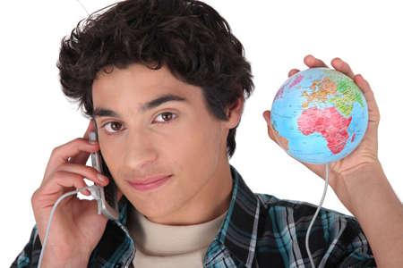 persona llamando: Hombre joven con su teléfono conectado en el mundo Foto de archivo