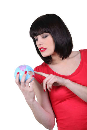 Brunette holding miniature globe photo