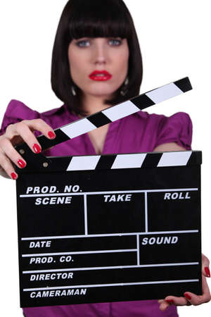 hinged: Woman holding up a clapperboard Stock Photo
