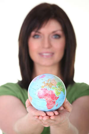 Woman in green holding planet earth photo