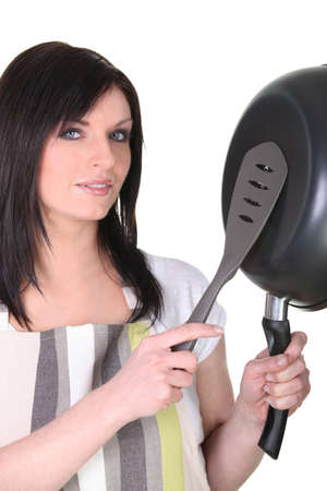 Woman with a spatula and a frying pan photo