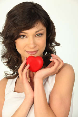 plastic heart: Young woman holding a plastic heart Stock Photo