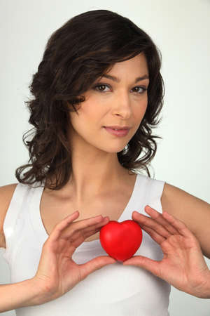Young brown-haired woman with red heart in hands Stock Photo - 18100220