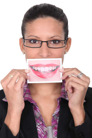 slicked: Woman holding up an enlarged picture of her mouth Stock Photo
