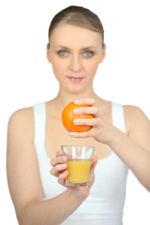 Woman squeezing fresh orange juice Stock Photo - 18089402