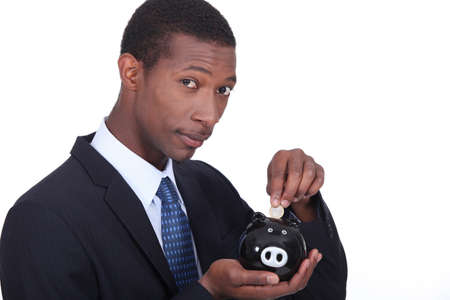 Man putting coins in piggy bank photo