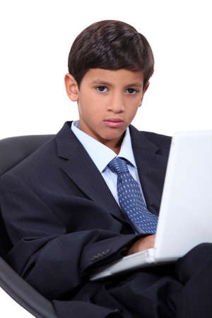 Serious young boy in an adult business suit with a laptop computer photo