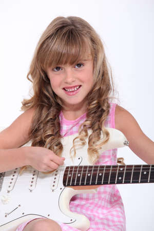 Little girl playing guitar photo