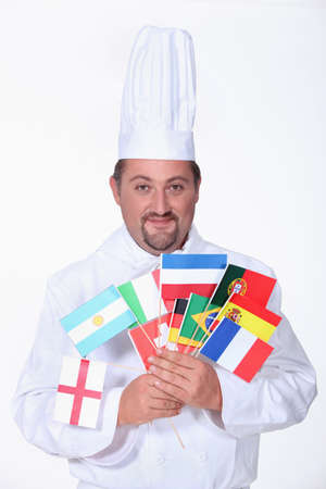 notorious: a chief cook holding a lot of foreign flags Stock Photo