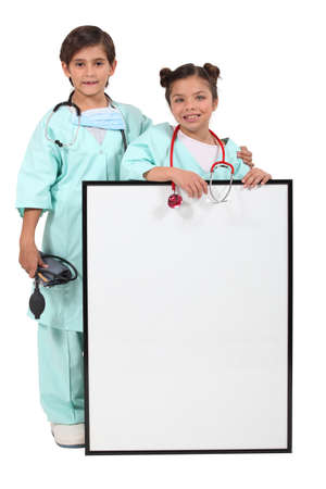 Children dressed up as doctors and standing behind a blank sign photo