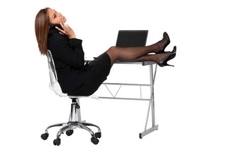 executive assistants: sexy employee dressed in black suit smiling on phone and stretching out her legs on her desk Stock Photo