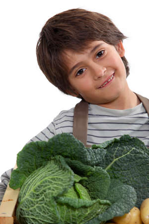 Young boy with a box of vegetables photo
