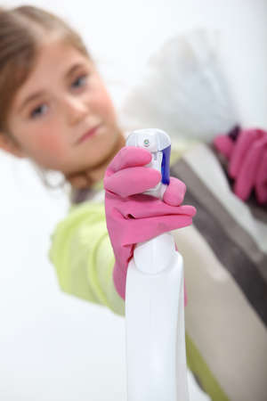 Little girl spraying cleaning product photo