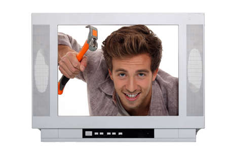 Concept image of a man hammering inside a television photo