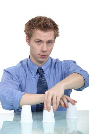deceit: A businessman doing a cup trick.