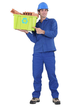 eagerness: Eager tradesman pointing to a recycling bin Stock Photo