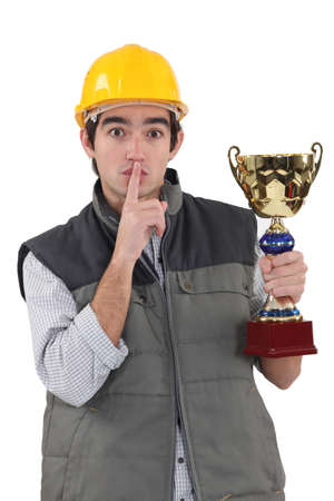 shushing: A construction worker shushing while having a trophy cup in his hand.
