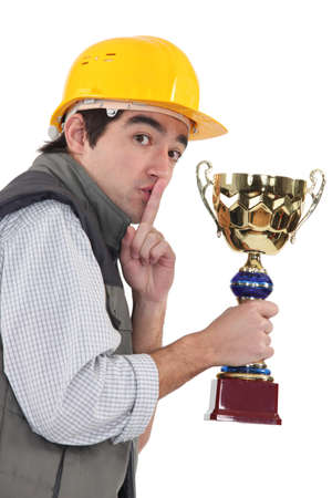 cheat: Secretive construction worker with a trophy Stock Photo