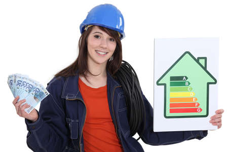energy efficient: Electrician holding cash and an energy rating sign Stock Photo
