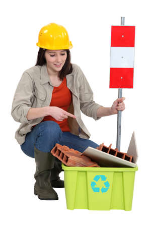 Female builder pointing to  waste photo