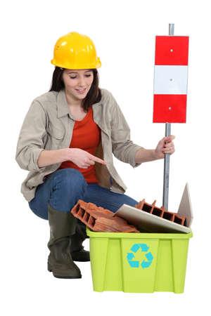 hazardous waste: Female builder pointing to  waste