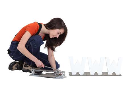 mujer arrodillada: Mujer con un cortador de azulejo Foto de archivo