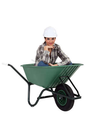 tradeswoman: Tradeswoman sitting in a wheelbarrow Stock Photo