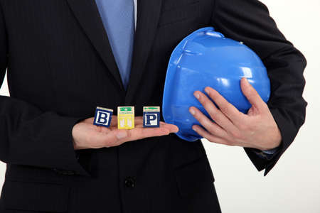 btp: Businessman holding a hard hat and letter blocks Stock Photo