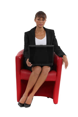 designer chair: Businesswoman sat in designer red leather chair Stock Photo