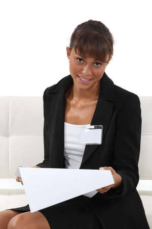 Businesswoman wearing an ID badge and reading a document photo