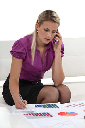 miniskirt: Worker writing notes whilst on the phone Stock Photo