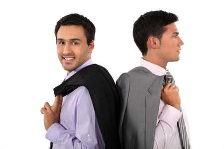 over shoulders: Two businessmen with jackets over shoulders Stock Photo