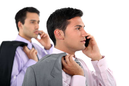 over shoulders: Two businessmen with jackets over shoulders making phone calls