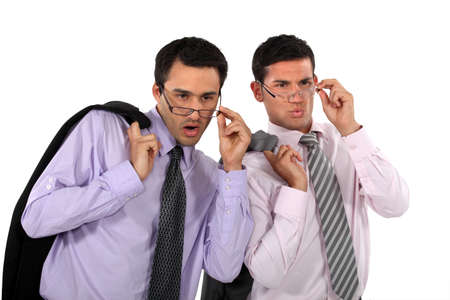 hard bound: Businessmen looking over their glasses at something Stock Photo