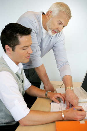 younger: Older man pointing out something in a document to a colleague Stock Photo