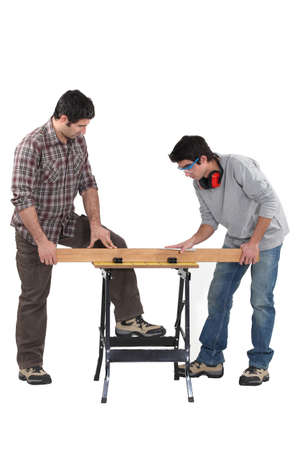 Father and son securing plank of wood photo