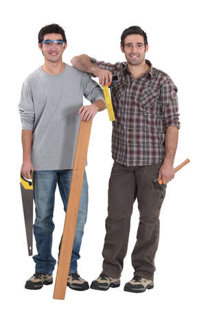 Two carpenters stood with plank of wood Stock Photo - 18272874