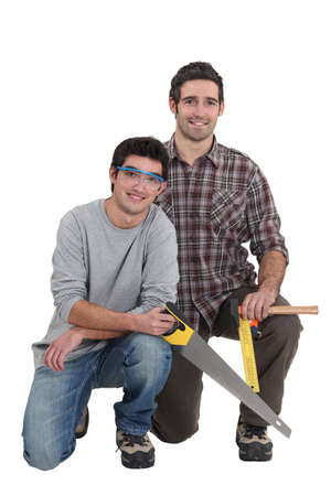 Carpenter and apprentice kneeling photo