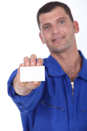 tradesperson: Man in blue overalls holding a business card left blank for your details Stock Photo
